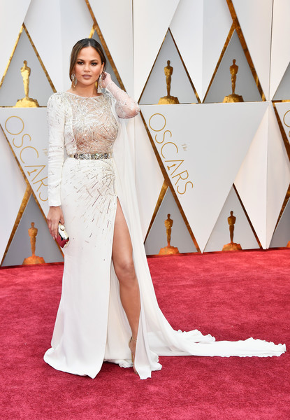 Chrissy Teigen in a Caped White Gown With Gold Embellishment