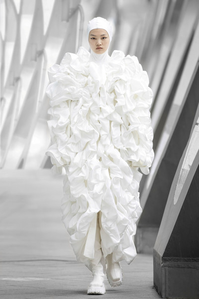 Annakiki at Milan Fall 2021 [face,dress,human body,sleeve,petal,runway,waist,gown,bridal clothing,fashion design,gown,wedding dress,dress,outerwear,fashion,clothing,fashion model,milan fashion week,wedding,fashion show,wedding dress,fashion show,haute couture,gown,fashion model,fashion,outerwear / m,dress,clothing,wedding]
