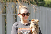 Miley Cyrus, with her hair in a bun and wearing Nike trainers, shows off her adorable dog outside of her home in Toluca Lake. The 18 year old actress and singer, who has just finished filming 'So Undercover,' was seen spending time with her co-star, Josh Bowman. They were spotted cuddling in Los Angeles this past week.